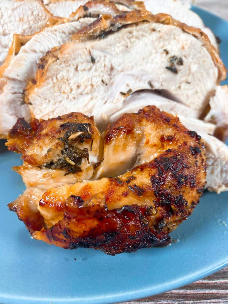 slices of seasoned turkey cooked in an air fryer sit on a blue plate