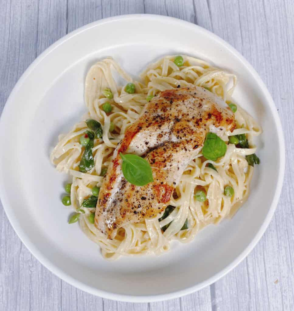 pan seared chicken sits on top a bed of pasta in a basil cream sauce