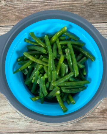 freshly blanched green beans sit in a colander