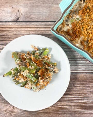 one serving lighter green bean casserole on a white plate with the teal casserole dish behind it