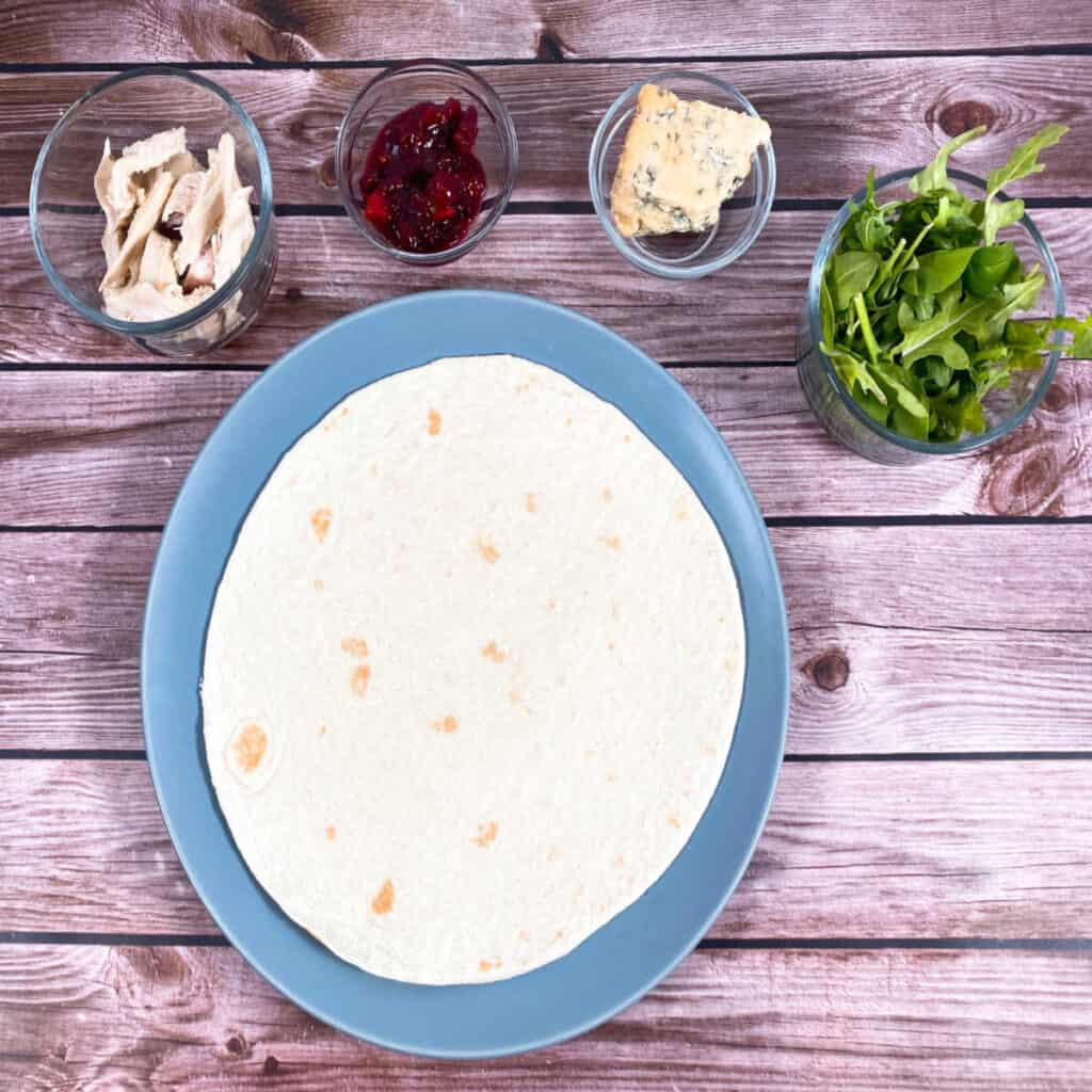 Ingredients for thanksgiving turkey cranberry wrap – turkey, cranberry sauce, blue cheese, arugula and a soft flour tortilla