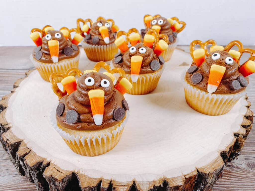 cupcakes are made into adorable thanksgiving turkeys by using pretzels, candy corn, chocolate chips and candy eyes