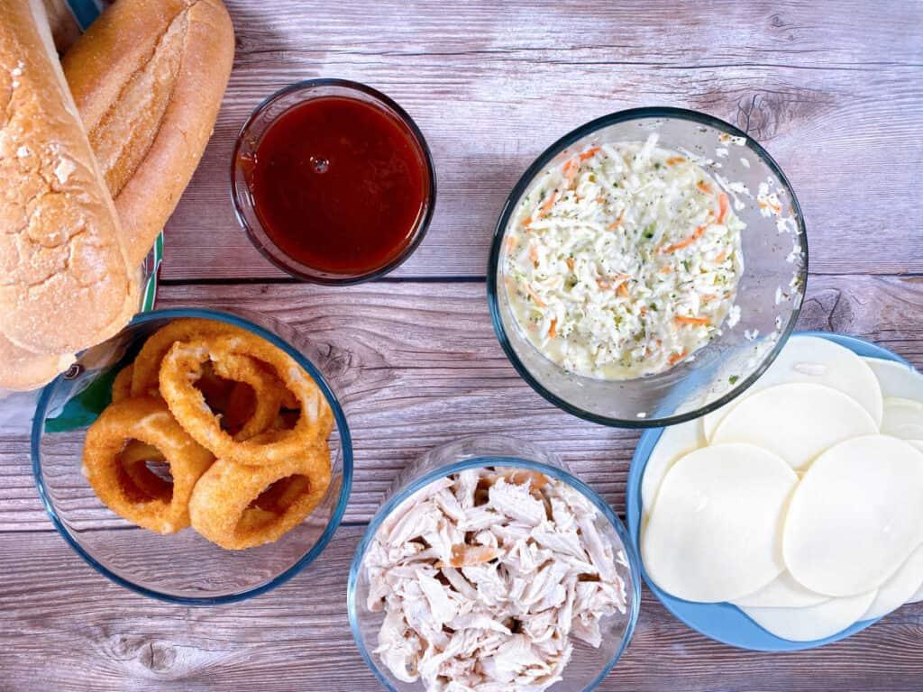 Ingredients for turkey slub sandwich – shredded turkey, barbecue sauce, provolone cheese, coleslaw, onion rings and sub rolls.