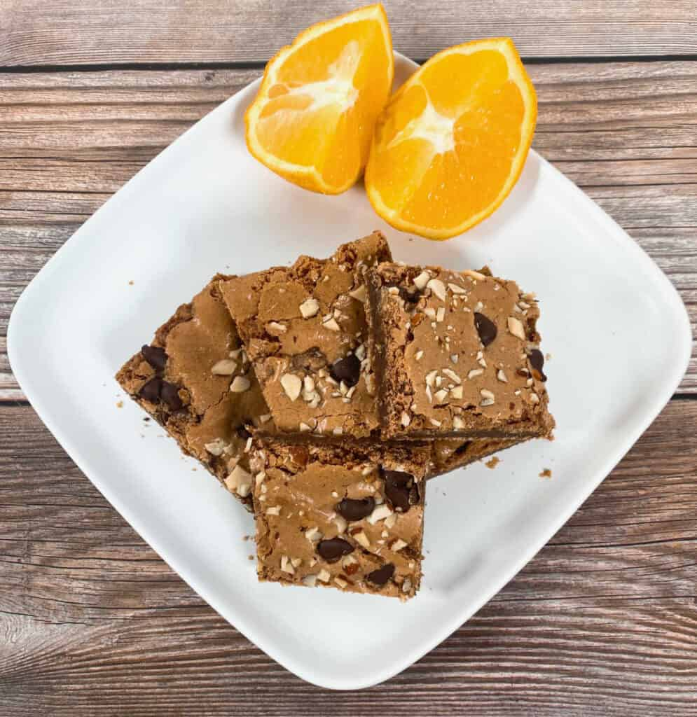 stacked almond orange brownies on a white plate with orange segments in the background