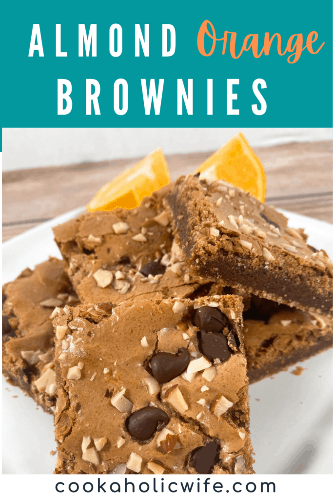 A white plate has a high stack of Almond Orange Brownies. Behind the brownies sits orange segments.