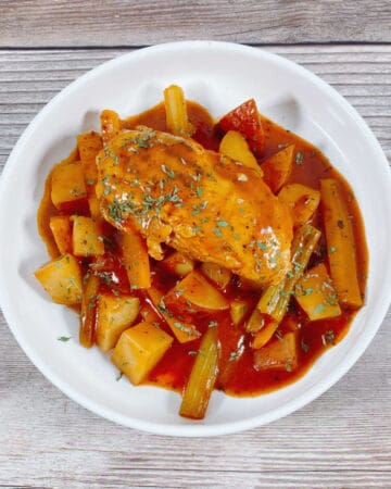 on a wooden background with a tan napkin sits a white bowl of braised chicken; chicken, carrots, celery and potatoes in a tomato broth.