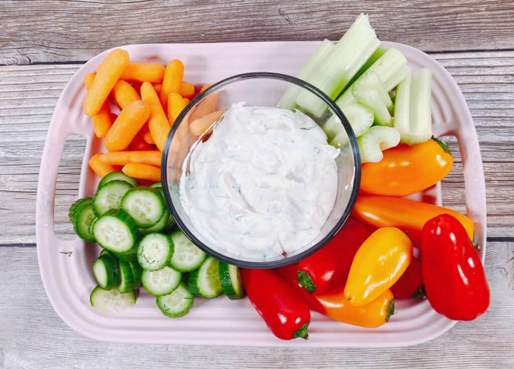 bowl of lighter veggie dip sits surrounded by carrots, celery, cucumbers and bell peppers
