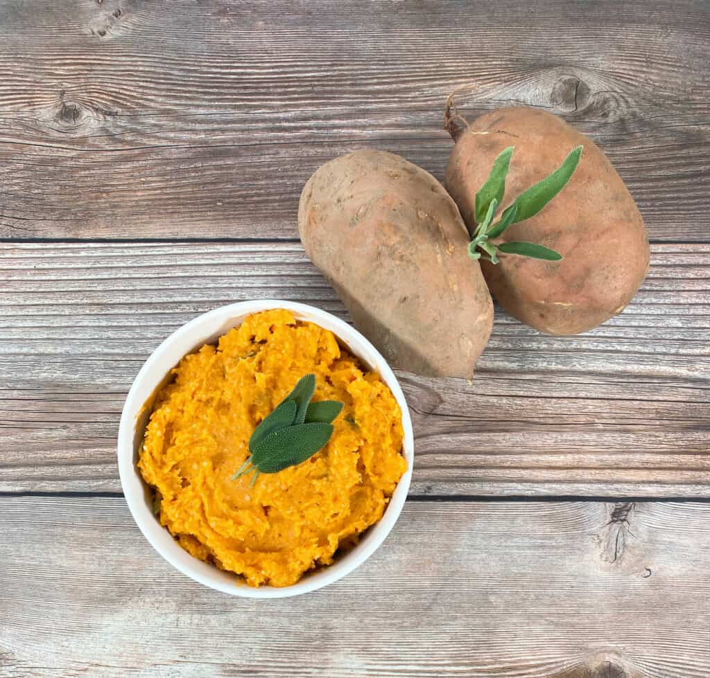 mashed sweet potatoes in a white bowl, topped with fresh sage leaves. Beside it, raw sweet potatoes.