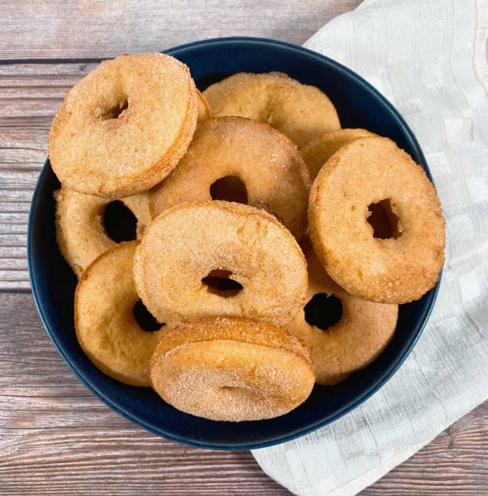 in a shallow navy blue bowl on a wooden background sits a pile of cinnamon sugar baked donuts