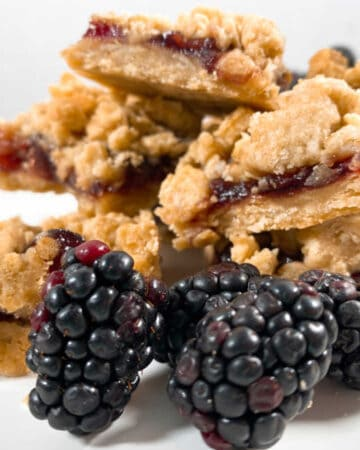stacked up blackberry oat crumble bars sit on a white plate with fresh blackberry sprinkled around them