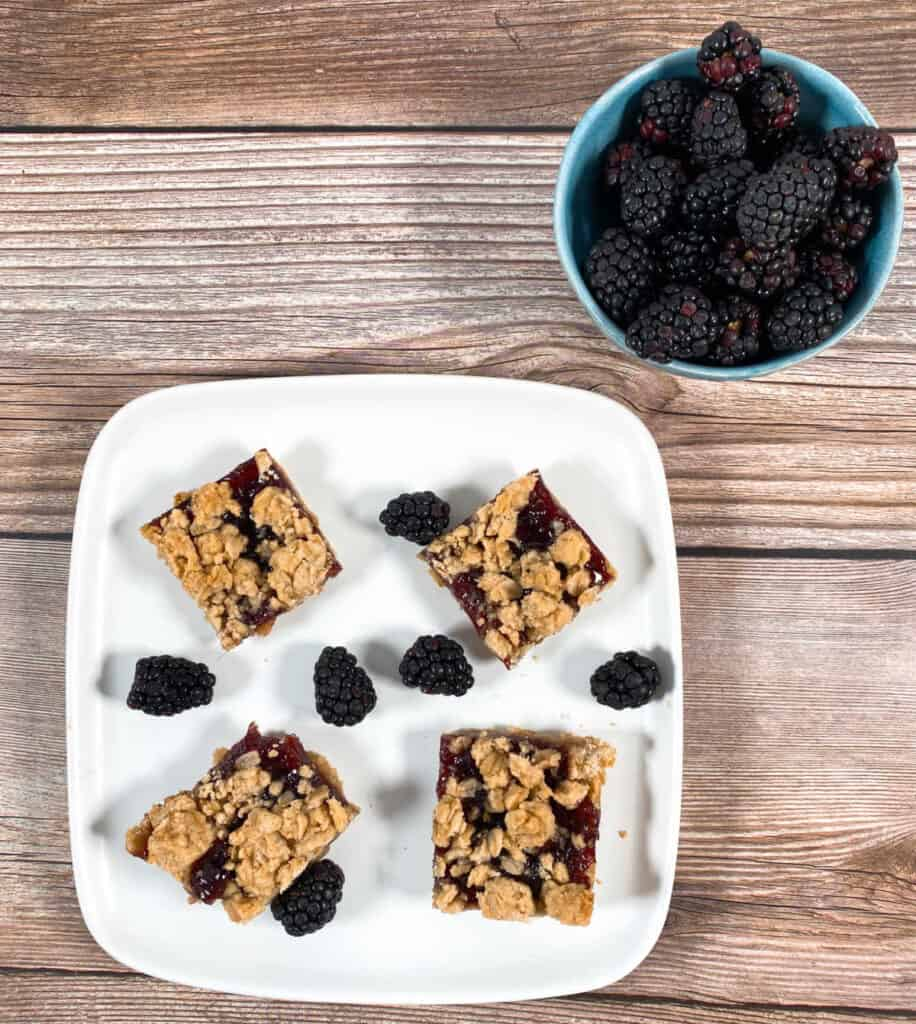 A white plate of blackberry crumble bars with fresh blackberries sits on a wooden background. To the left is a bowl of fresh blackberries