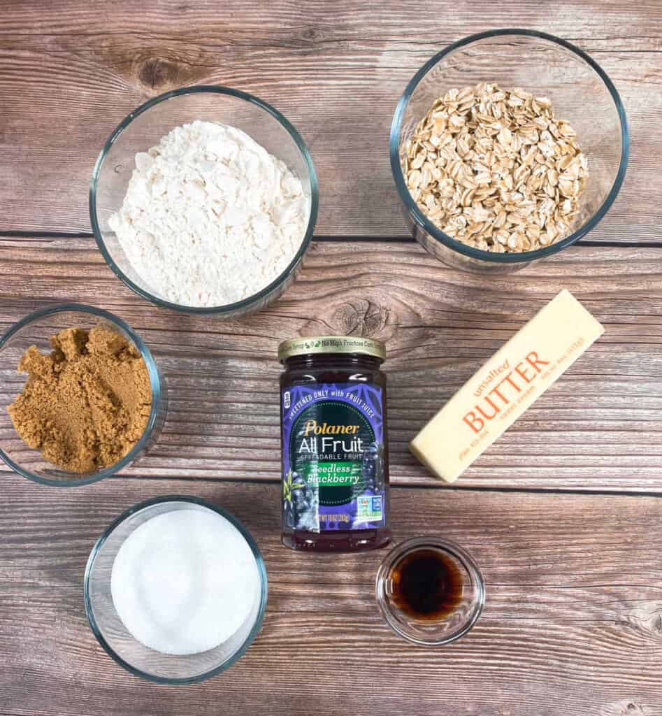 ingredients for blackberry oat crumble bars on a wooden background - all purpose flour, brown sugar, granulated sugar, old fashioned oats, butter, vanilla and blackberry preserves