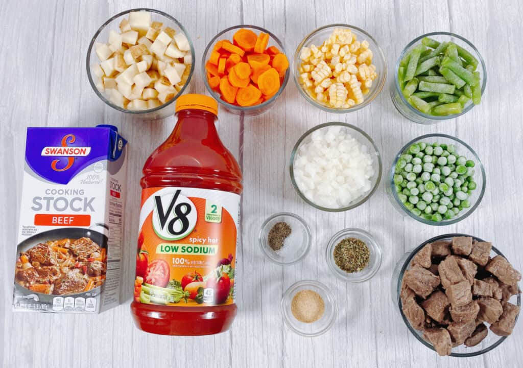 ingredients for grandma's beef and vegetable soup sit on a white wooden background. Top row - diced potatoes, carrots, corn and green beans in glass dishes. Bottom row - carton of beef stock, container of V8 spicy vegetable juice, bowl of diced onions, bowl of frozen peas, bowl of beef cubes and small containers holding salt, pepper, garlic powder and dried oregano.
