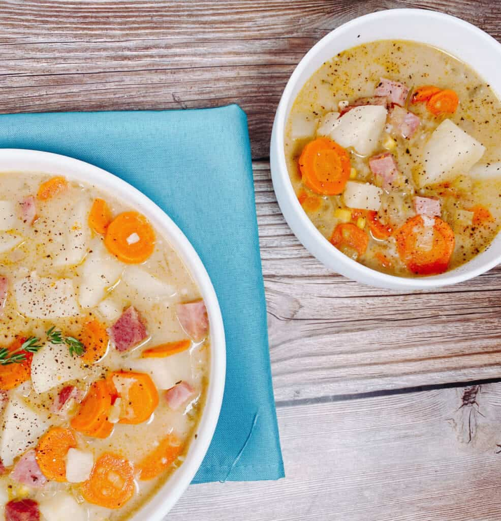 Two bowls of creamy ham and potato soup sit on a wooden background. The bowl on the left sits under a turquoise napkin. In both bowls, pieces of ham, potato, carrots and veggies are prominent over the broth. Both bowls of soup are seasoned with salt and pepper and the left bowl has a sprig of fresh thyme.