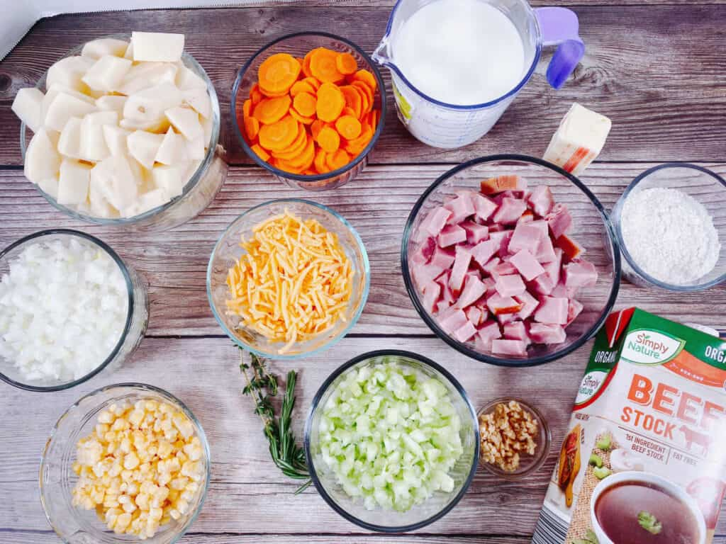 Ingredients for creamy ham and potato soup. Ingredients are potatoes, carrots, celery, onion, corn, ham, cheese, milk, butter, flour, beefr broth, garlic, rosemary and thyme.