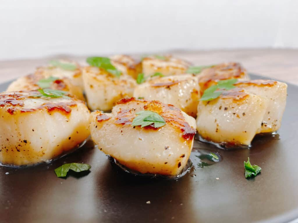 side view of scallops on a black plate