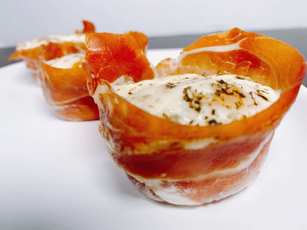 Crispy prosciutto wraps around an oven-baked egg cup, topped with mozzarella cheese and italian seasoning.