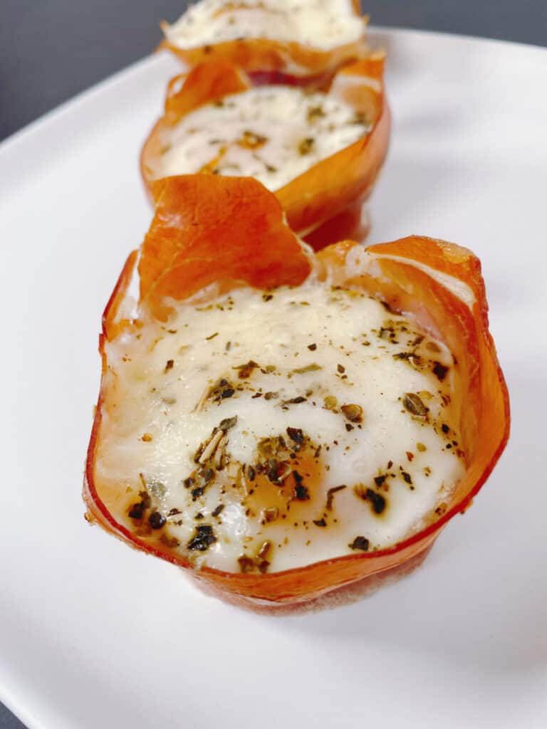 on a white plate sits two prosciutto egg cups - prosciutto is wrapped around the oven-baked egg topped with mozzarella cheese and Italian seasoning