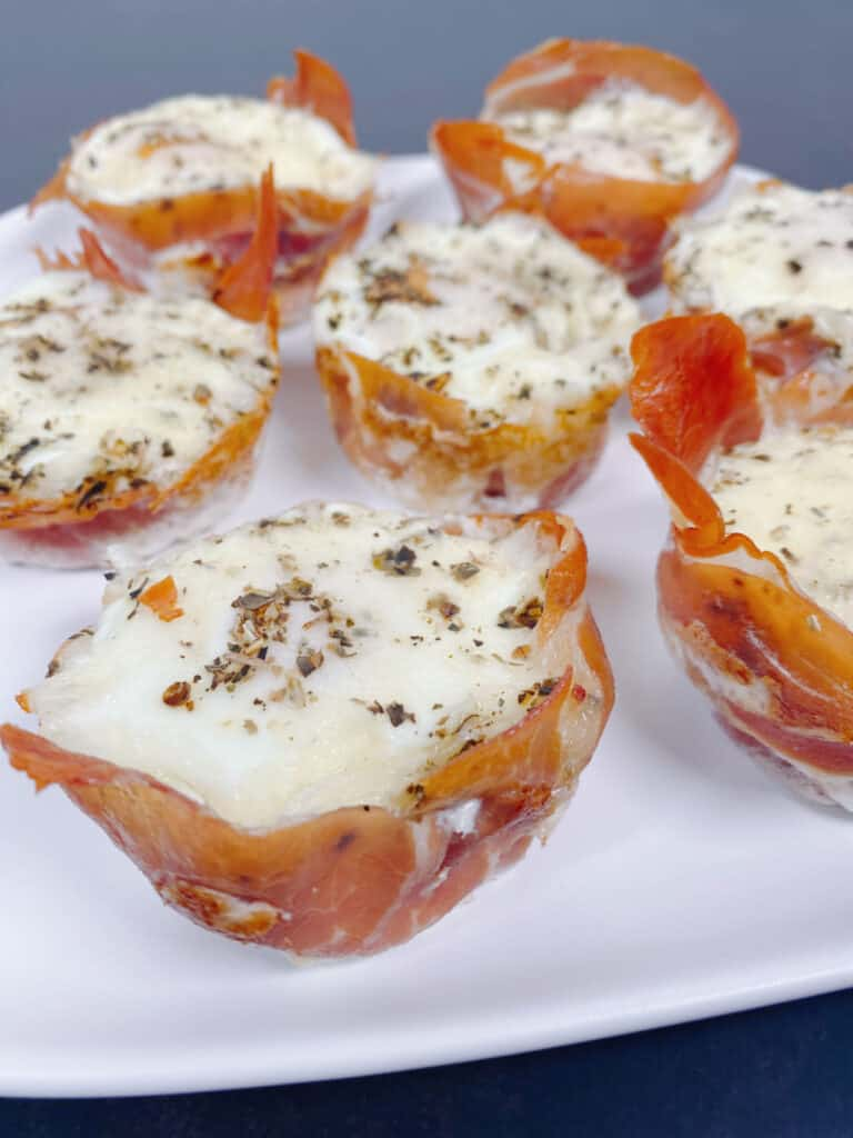 White plate of prosciutto egg cups - prosciutto wrapped around an oven-baked egg thats topped with mozzarella cheese and italian seasoning