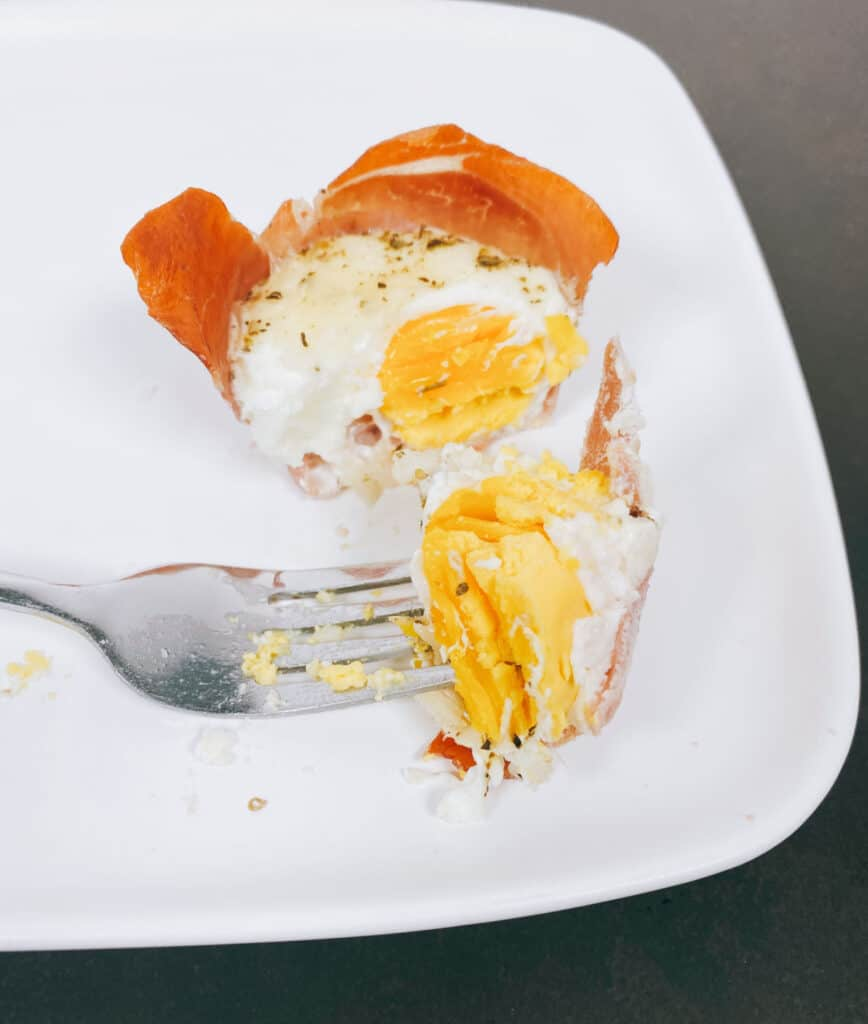on a white plate sits a prosciutto egg cup cut open to show the soft boiled yolk inside. the top has melted mozzarella cheese and italian seasoning