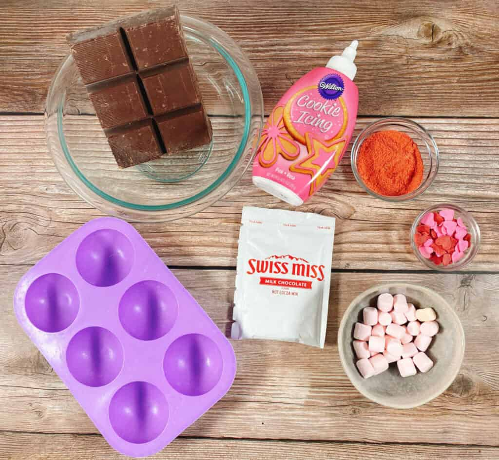 Ingredients for strawberry hot chocolate bombs sit on a wooden background. Ingredients include a silicone spherical mold, chocolate almond park, hot chocolate powder mix, powdered freeze dried strawberries, pink cookie icing. strawberry marshmallows and pink heart sprinkles.