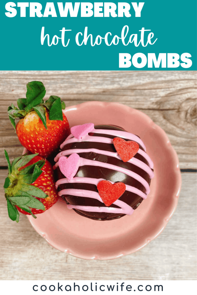 Close up image of a strawberry hot chocolate bomb sitting on a small pink stand with fresh strawberries.