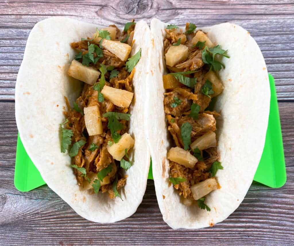 Two tacos sit in a taco stand on a wooden background. Flour tortillas are filled with the shredded, al pastor pork and are topped with pineapple, cilantro and onion.