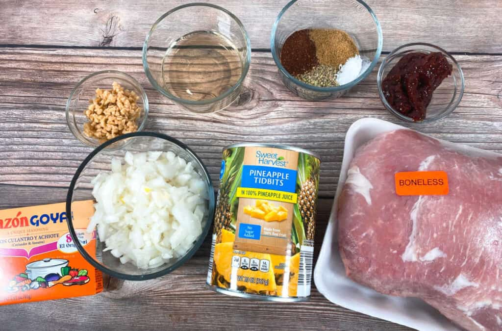 Ingredients for tacos al pastor sit in glass bowls on a wooden background. Ingredients are pork shoulder, canned pineapple, onion, vinegar, chiles in adobo, garlic, oregano, salt and Goya Sazon. To complete the meal, tortillas, cilantro and additional onion and pineapple are needed.