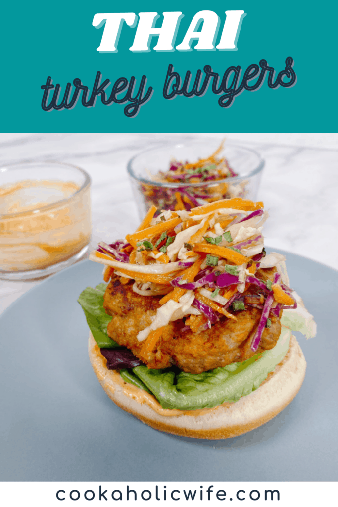 Thai Turkey Burgers: colorful asian slaw of carrots and cabbage sits on top of a thai-flavored turkey burger. Underneath is a bed of green leaf lettuce and the burger bun is slathered with a spicy sriracha mayo. All sitting on a blue plate. In the background are bowls with the asian slaw and spicy mayo.