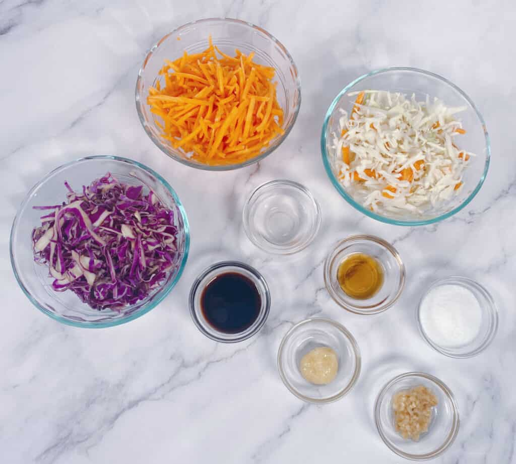 Ingredients for Asian Slaw to top the Thai Turkey Burgers sit in glass bowls on a marble background. Ingredients are green and purple cabbage, carrots, soy sauce, garlic, ginger, rice vinegar, sesame oil and sugar,