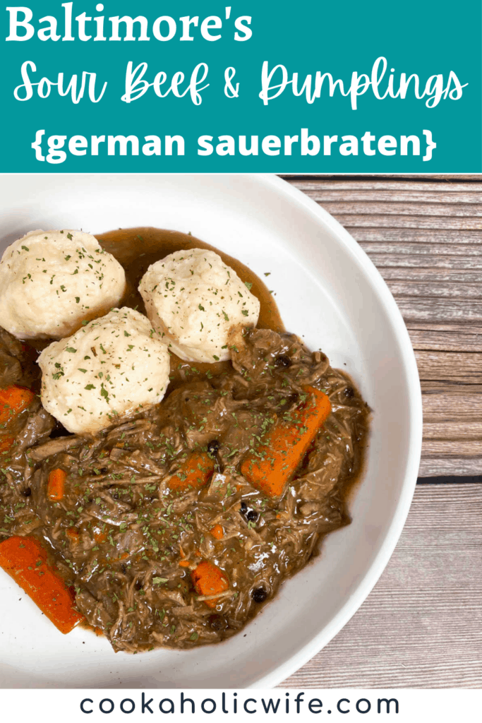 A shallow white dish sits on a wooden background. At the top left of the dish sits homemade potato dumplings sprinkled with fresh parsley and under that is the sour beef and carrots, shredded beef, in a pot roast style.