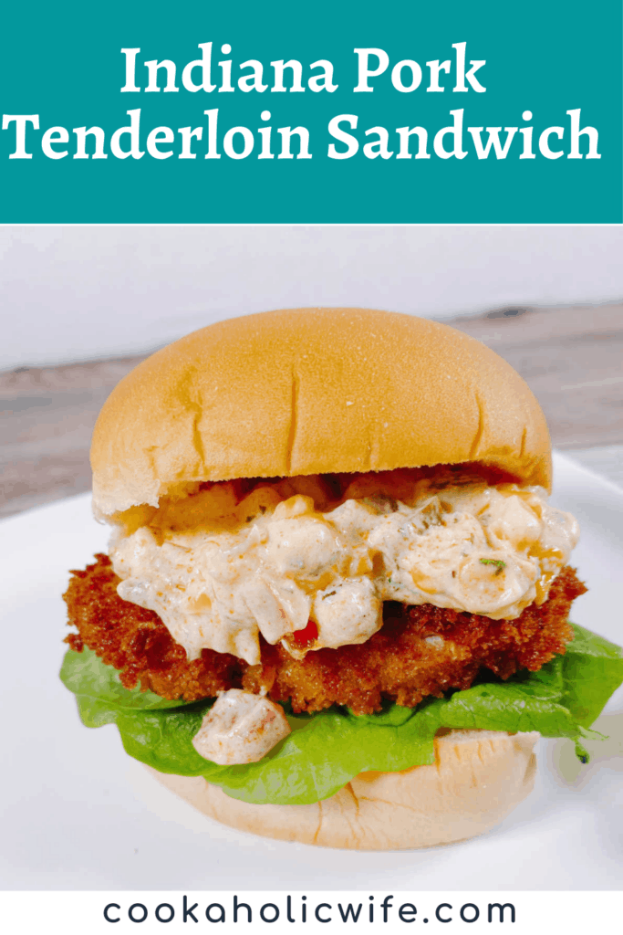 Indiana Pork Tenderloin Sandwich - on a white square plate sits the sandwich. The cheesy corn relish is spilling down the sandwich onto the plate. Under the relish is a crispy, fried piece of pork, a bed of lettuce and the bottom half of the burger bun.