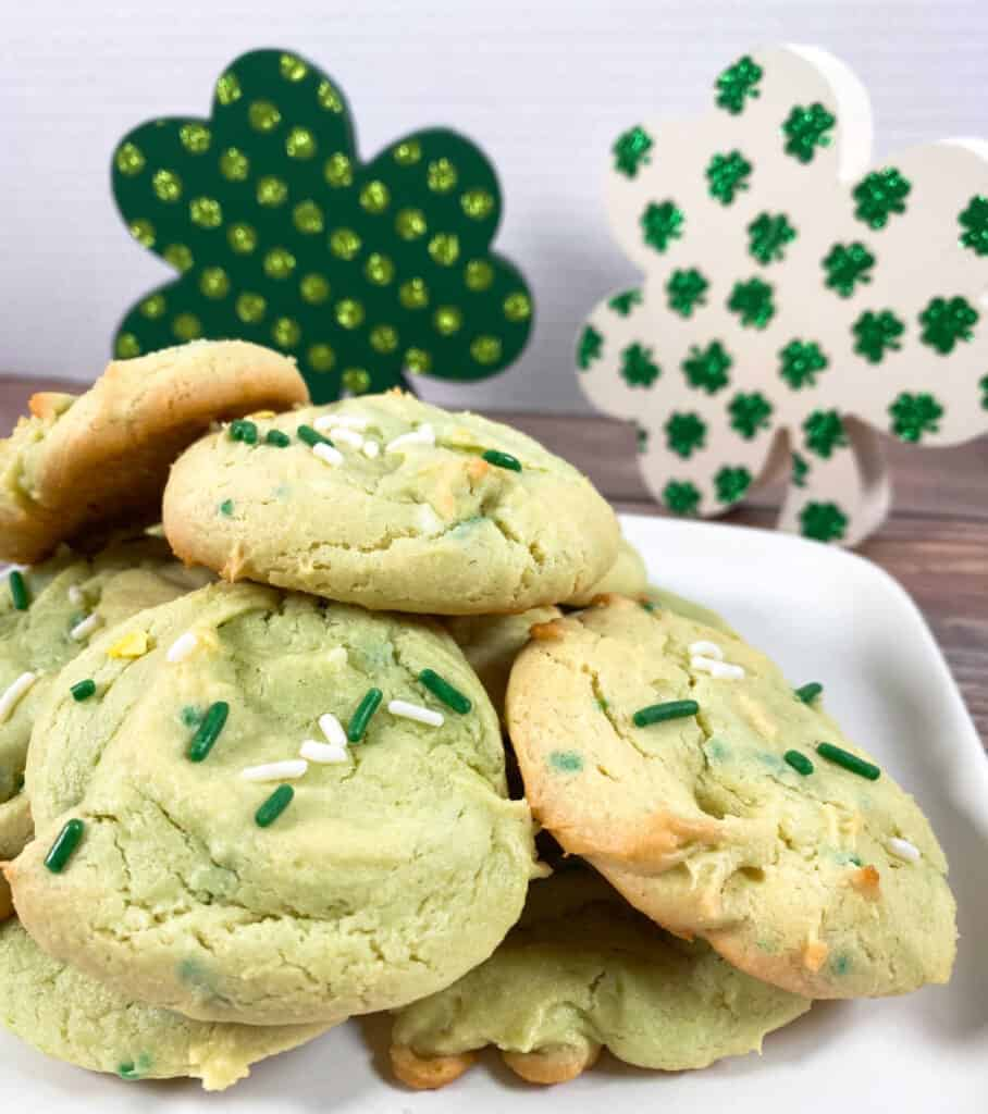 green hued cake mix cookies topped with sprinkles sit on a white plate with white and green wooden shamrock decorations behind them.