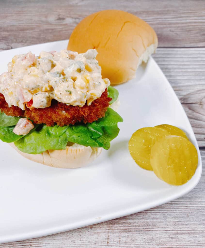 Open-faced view of the sandwich, with a heaping pile of the creamy corn relish sitting on top a piece of crispy, fried pork on a burger bun. Pickles sit off to the side of the sandwich.