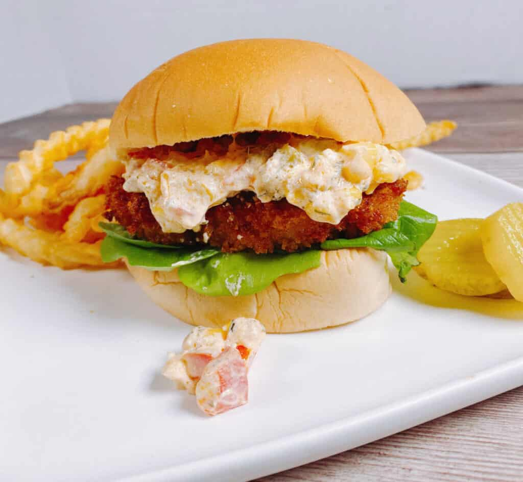 Indiana pork tenderloin sandwich sits on a white plate - crispy fried pork sits on a burger bun with a cheesy corn relish on top. Some of the relish is spilling out onto the plate. Behind the sandwich sits french fries and pickles.