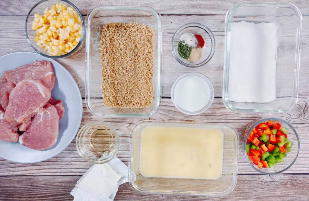 Ingredients for indiana pork tenderloin sandwich sit on a wooden background. Sliced and pounded thin pork loin, panko bread crumbs, Wondra flour, egg, corn, bell pepper, milk, vinegar, cream cheese and seasonings.
