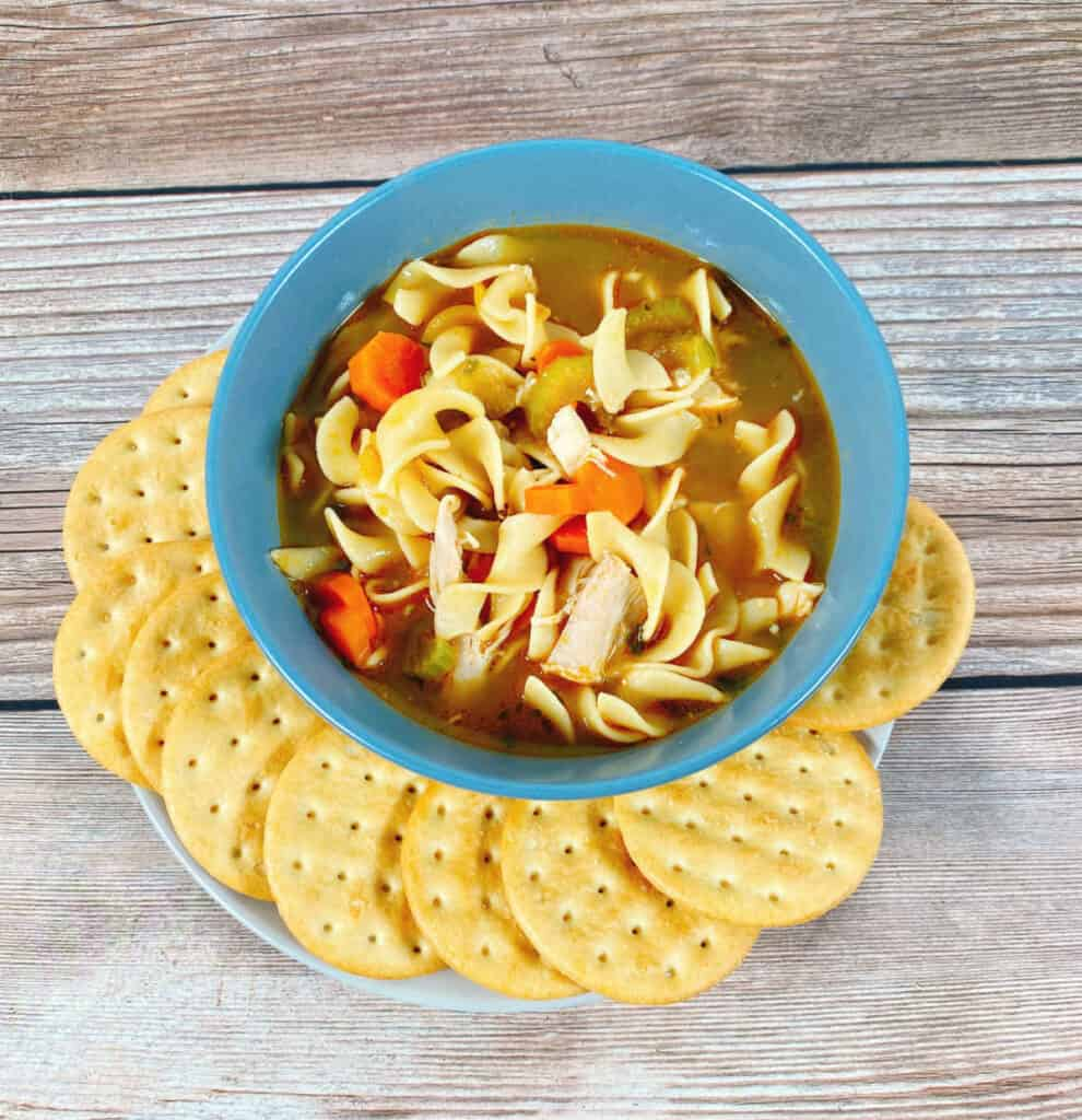 A hearty bowl of chicken noodle soup, full of shredded chicken, carrots and celery sits surrounded by crackers on a wooden background.