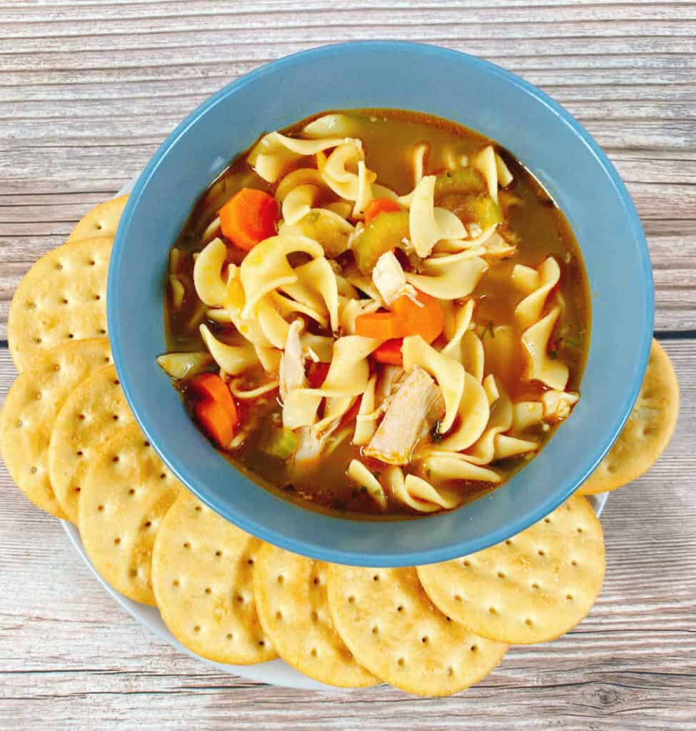 close up bowl of chicken noodle soup, with egg noodles, shredded chicken, carrots and celery visible. Round crackers surround the bowl and it's sitting on a wooden background.