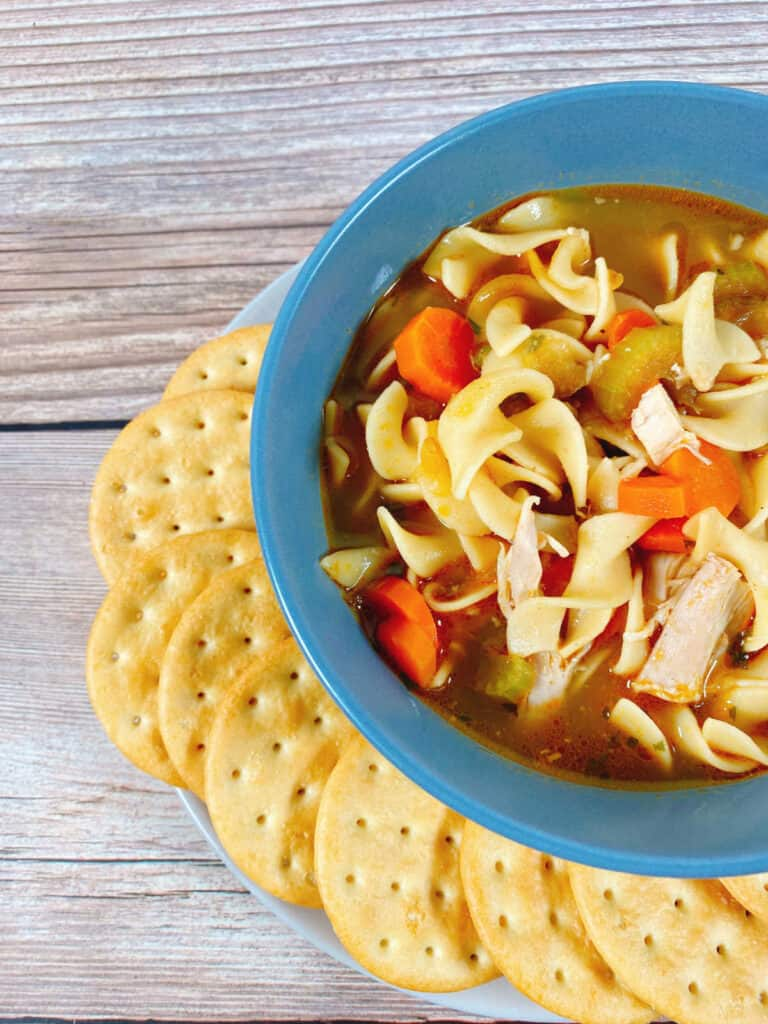 Side image of chicken noodle soup - close up of the soup, showing the carrots, noodles and chicken. Crackers sit next to the bowl.