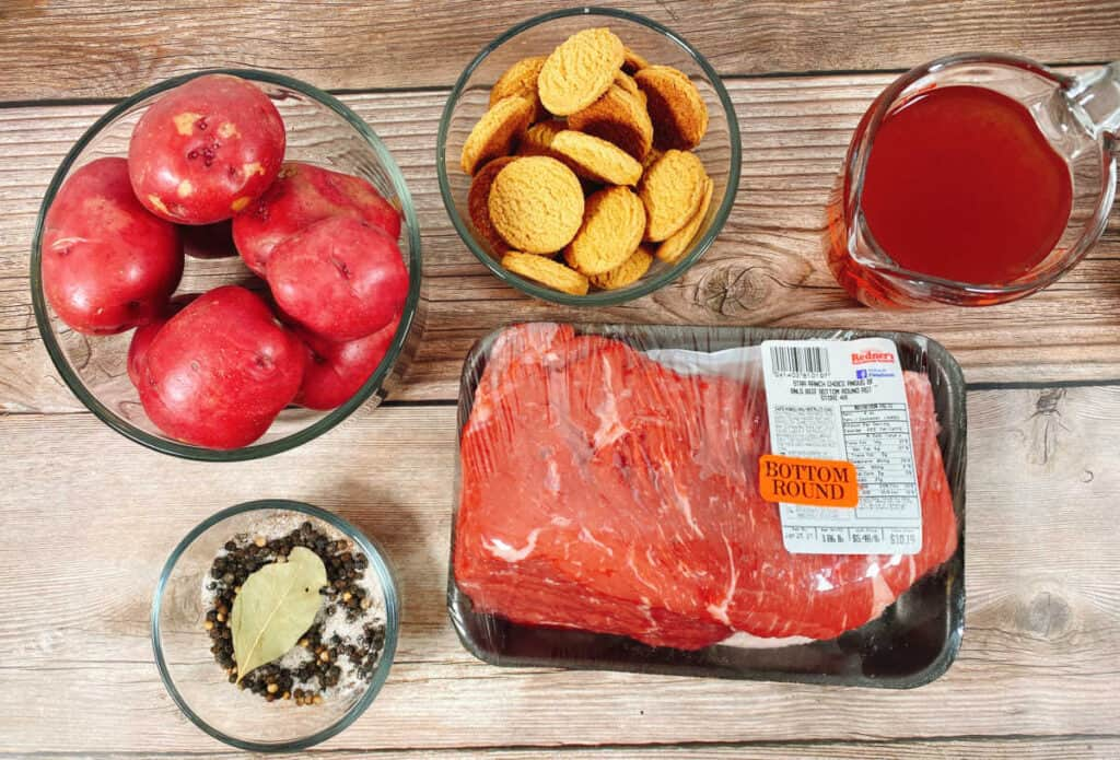Ingredients for sour beef and dumplings sit on a wooden background. Potatoes, gingersnap cookies, red wine vinegar, spices and beef roast. Not pictured, carrots and onions,