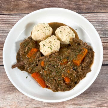 Baltimore's take on Sauerbrauten, a bowl of sour beef and dumplings sits on a wooden background. The gravy is made from gingersnap cookies