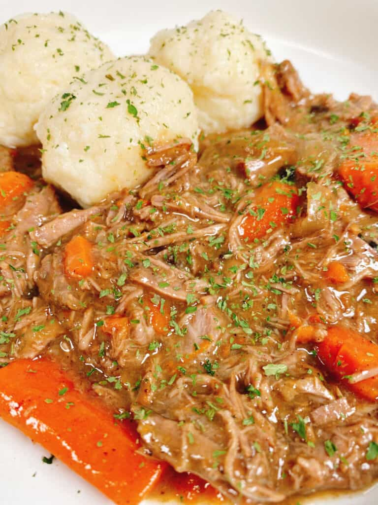 Close up picture of the sour beef and dumplings, the beef is shredded and mix in with the carrots and onions. The potato dumplings are in the back and the entire dish is sprinkled with fresh parsley.