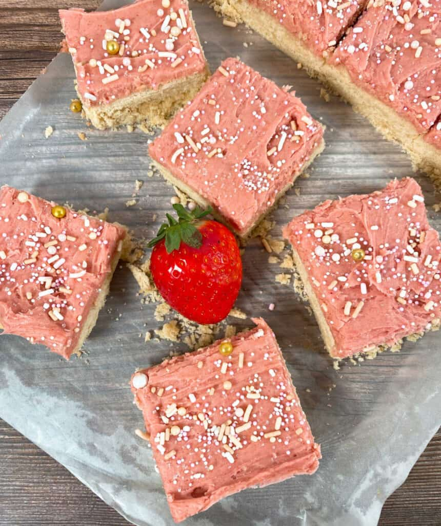 strawberries and cream cookie bars are cut into squares sitting on a piece of parchment paper on a wooden background. Frosting on the bars is pink and covered in sprinkles. a strawberry sits in the center of the bars.
