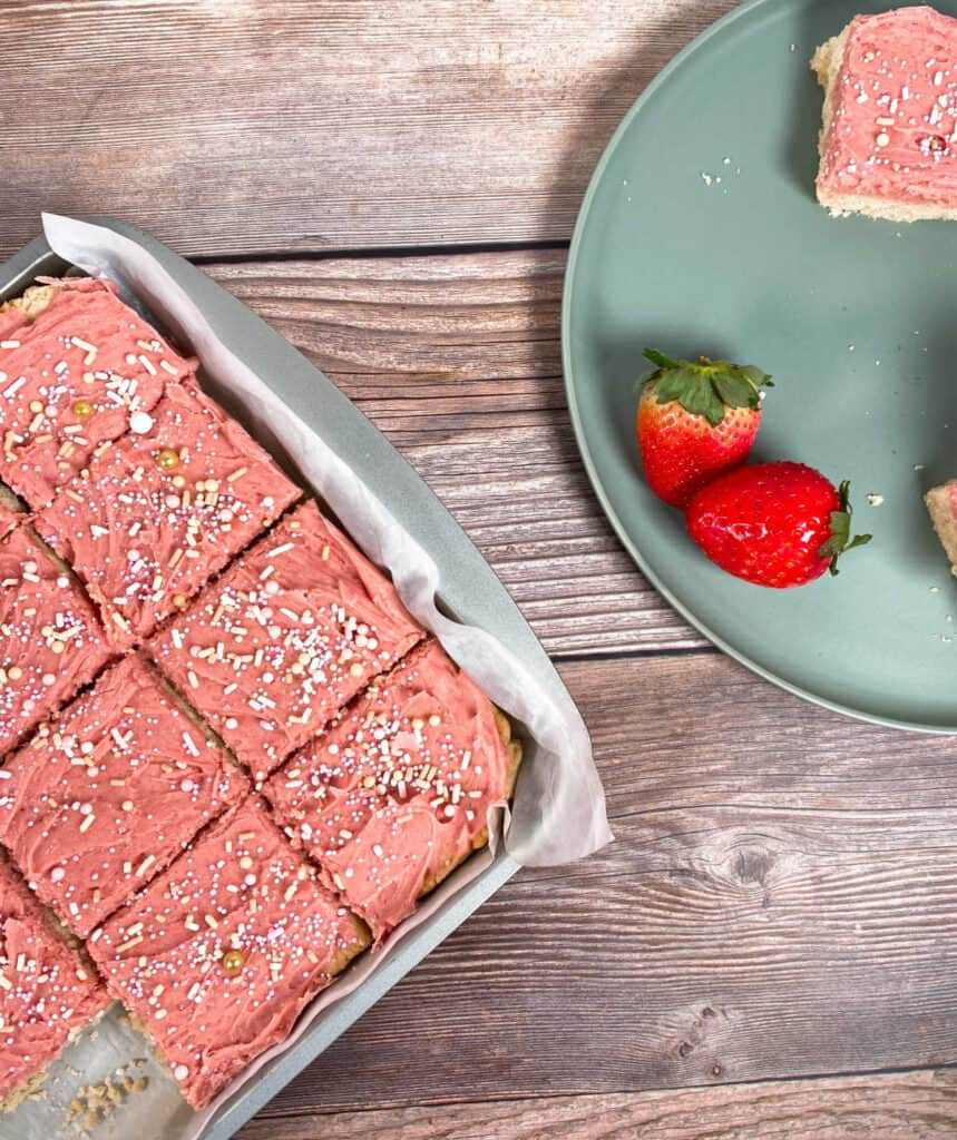on the left side of the image is strawberries and cream cookie bars in a baking dish, cut into squares. On the right are strawberries and some of the cut up cookie bar on a mint green plate.