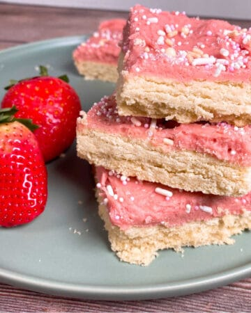 strawberries and cream cookie bars are stacked 3 high on a mint green plate with strawberries on the left. the plate is on a wooden background. The strawberry frosting of the cookie bars is pink and pink, white and gold sprinkles are on top.