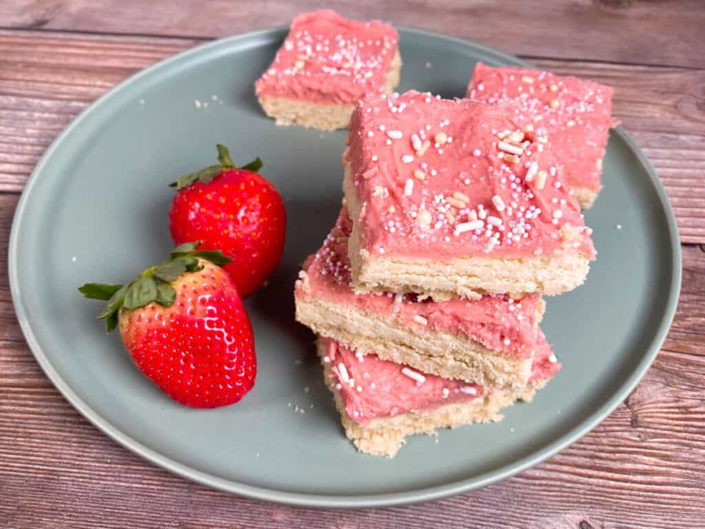 on a wooden background sits a mint green plate. three strawberries and cream cookie bars are stacked on top of each other and two more are in the background. two strawberries sit on the left side of the plate.