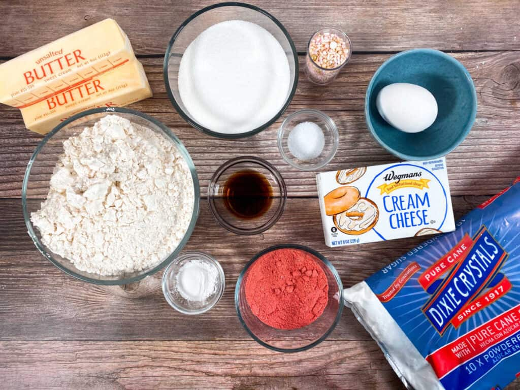 ingredients for strawberries and cream cookie bars - butter, flour, sugar, egg, vanilla, baking powder, cream cheese, freeze dried strawberry powder, powdered sugar, and sprinkles.
