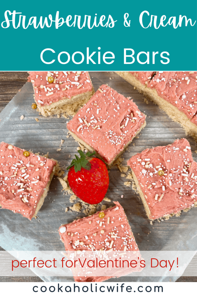 strawberries and cream cookie bars sit on a sheet of parchment paper with a strawberry in the center. bars are decorated with pink, strawberry frosting and sprinkles.