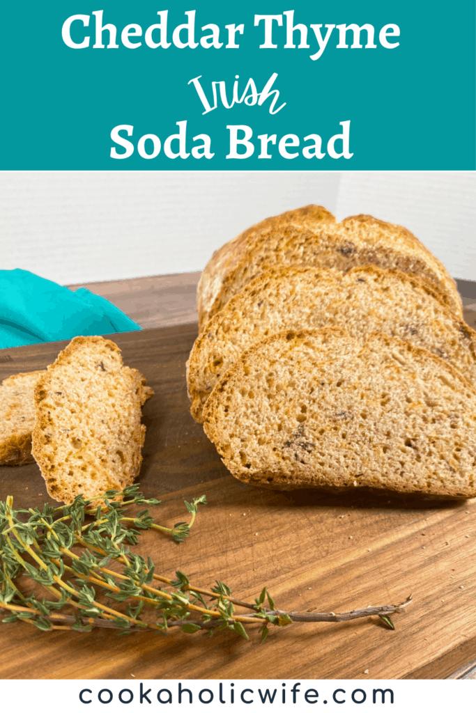 slices of cheddar thyme irish soda bread slt on a dark wooden cutting board. fresh thyme sits off to the side.