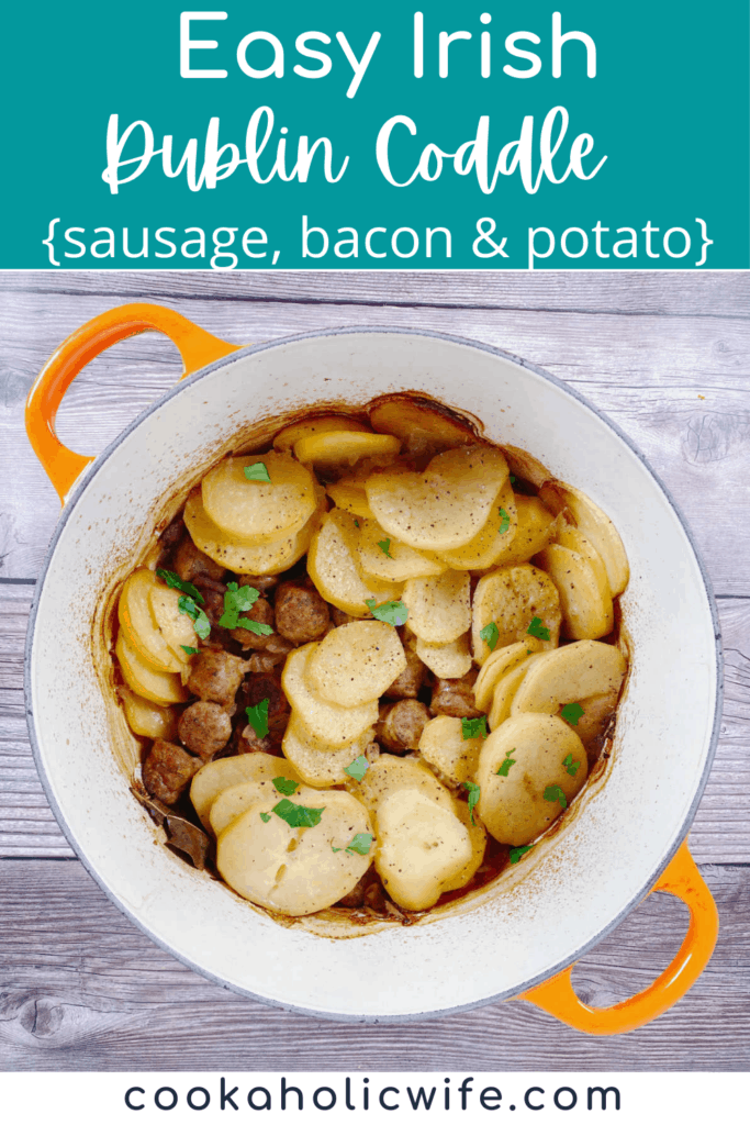 an orange dutch oven sits on a wooden background. The pot is full of pieces of sausage and bacon and sliced potatoes, garnished with parsley, making up this easy irish dublin coddle.